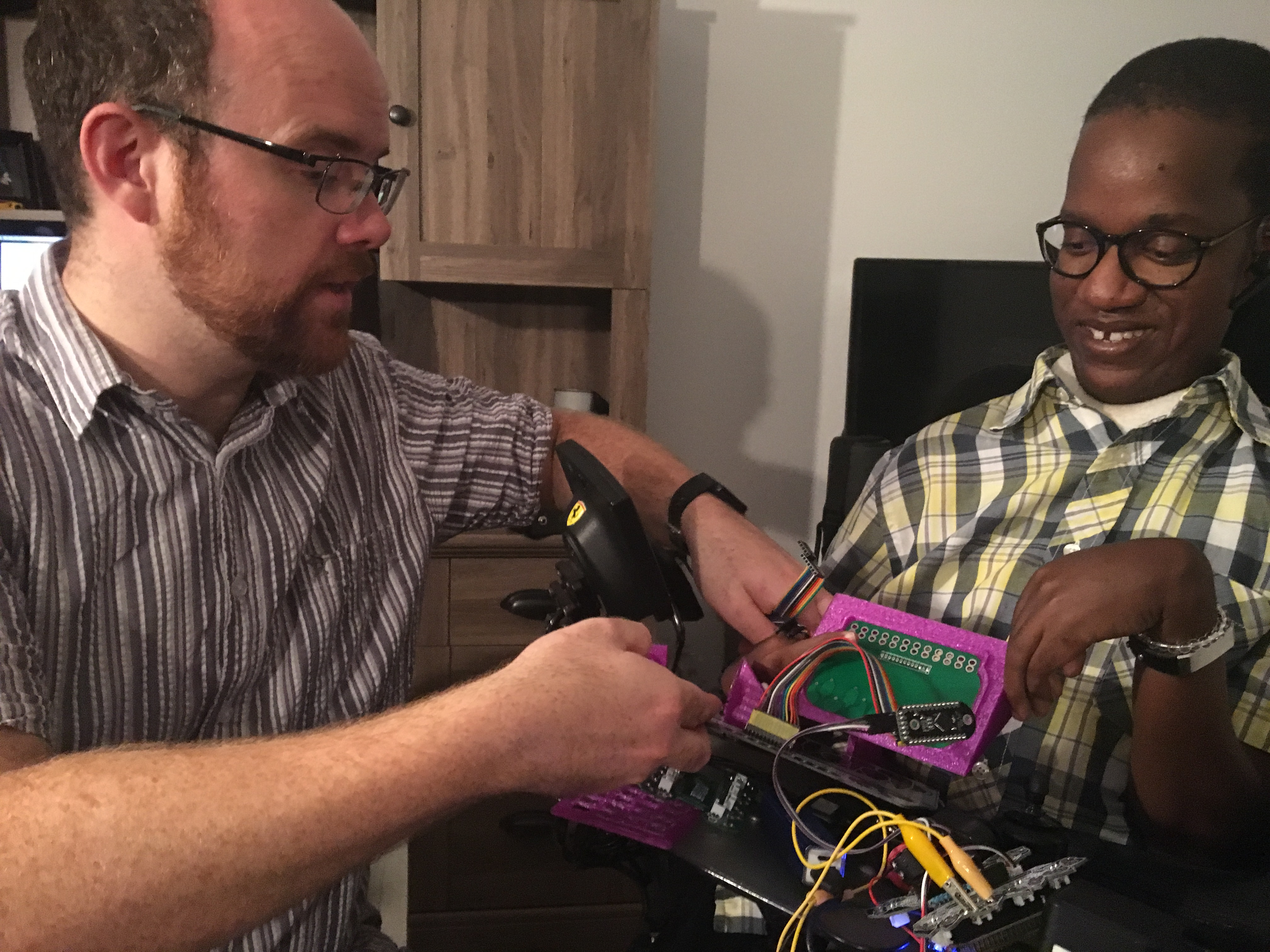 Charles and Gift holding a miniature keyboard made of 3D printed parts and a custom circuit board.